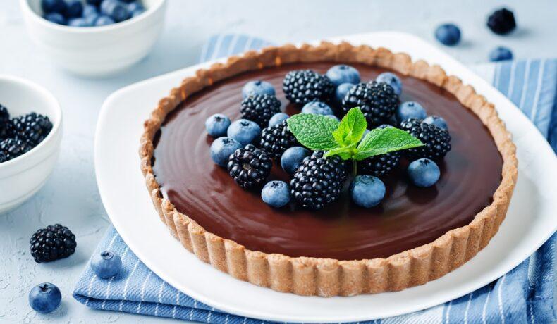 tartă cu ciocolată și fructe de pădure pe un platou alb