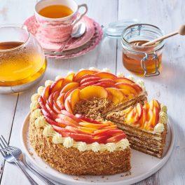 Tort Medovik secționat pe un platou alb, alături de cești cu ceai și un borcan cu miere