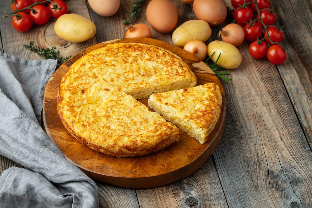 Tortilla, porționată pe un tocător de lemn, gata de servit, alături de roșii și cartofi