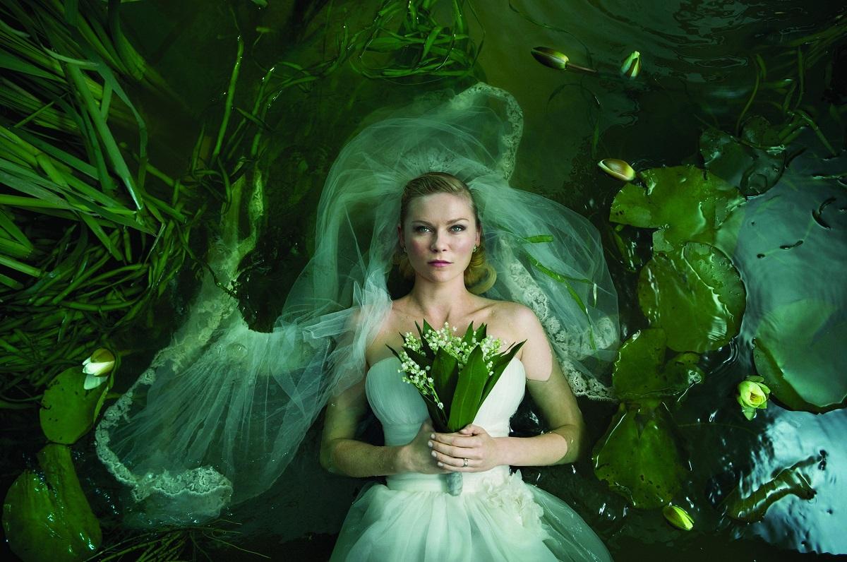 Kirsten Dunst în filmul Melancholia, 2011. E îmbrăcată ca o mireasă, cu un buchet de flori, într-un lac verde, cu nuferi