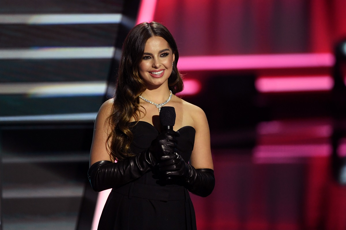 Addison Rae într-o rochie neagră fără bretele și cu mănuși negre în timp ce ține un microfon și se află pe scenă la Billboard Music Awards în 2020