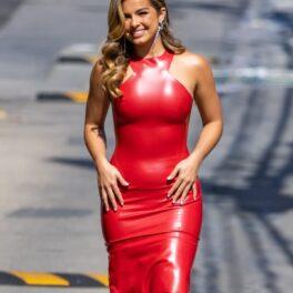 Addison Rae într-o rochie mulată roșie în timp ce stă cu mâinile pe șolduri și merge pe stradă la showul Jimmy Kimmel Live