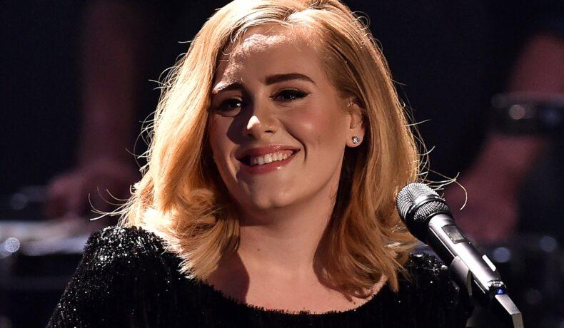 Portret al artistei Adele în timp ce zâmbește și are un față un micorfon la unul din concertele sale