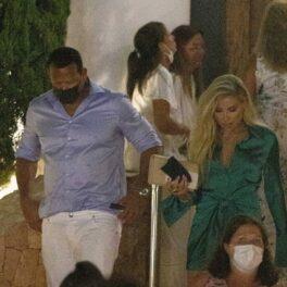 Alex Rogriguez la cămașă în dungi albastre și blugi albi, alături de Melanie Collins într-o rochie verde în timp ce coboară scările și merg la o petrecere în Ibiza