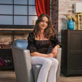 Fotografie cu Alexandra Iosif în timp ce se află pe platourile de filmare pentru interviul echipei CaTine.ro și poartă o bluză neagră cu mâneci bufante și o pereche de pantaloni albi.