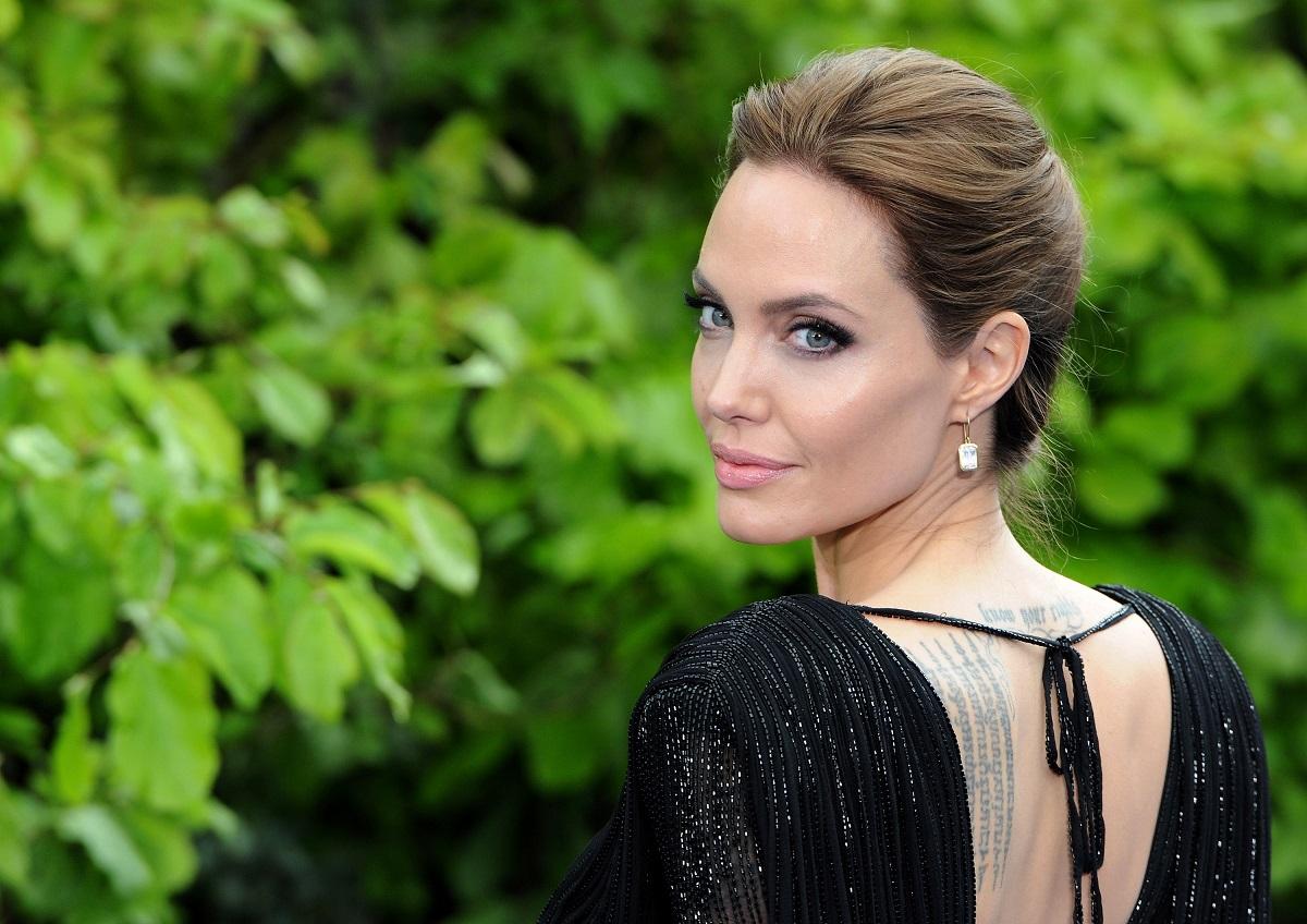 Angelina Jolie în timp ce poartă o rochie neagră și stă întoarsă cu capul spre cameră zâmbind la premiera oficială a filmului Maleficent din 2014