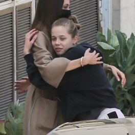 Shiloh Jolie-Pitt într-un hanorac negru în timp ce o strângeîn brațe pe mama sa, Angelina Jolie, care poartă un trench maroniu
