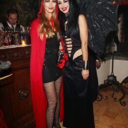 Beatrice Borromeo într-un costum de Halloween cu o rochie neagră și o capă roșie alături de prietena sa care poartă o rochie neagră la o petrecere privată de la Hollywood din anul 2012