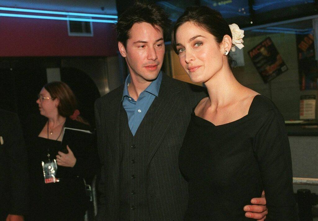 Keanu Reeves alături de Carrie Anne Moss în timp ce se țin îmbrățișați la premiera din Australia a filmului The Matrix din 1999