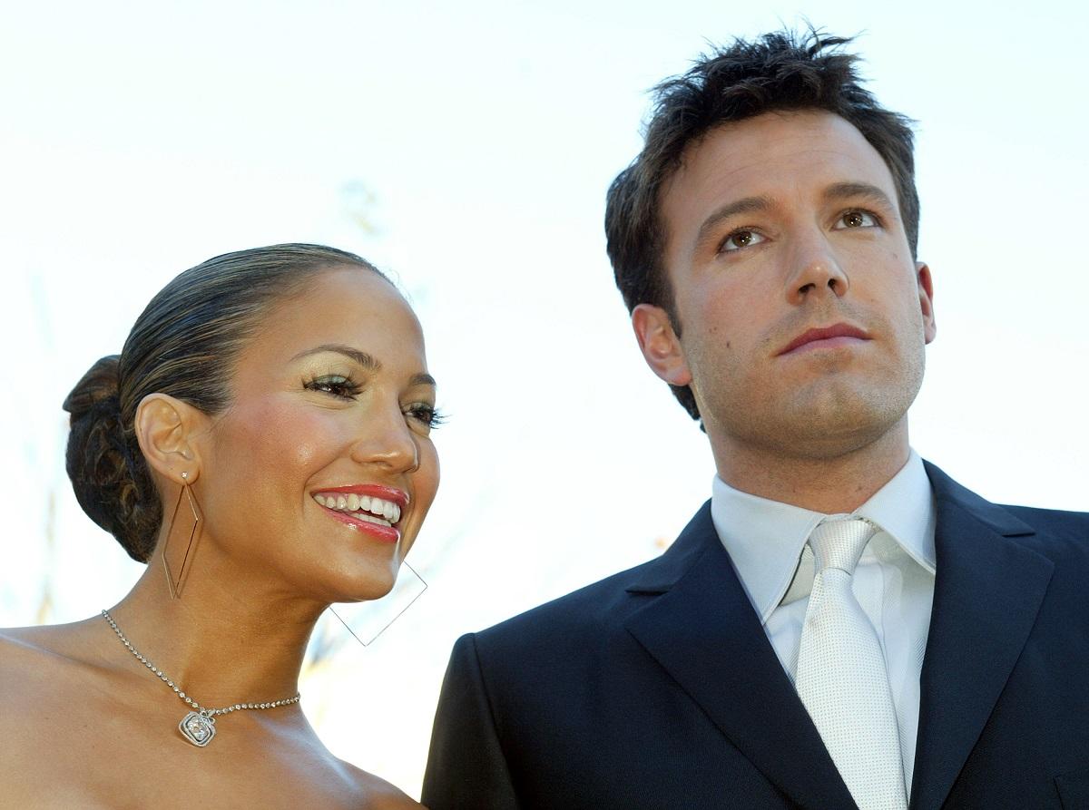 Jennifer Lopez cu părul prins în coc în timp ce zâmbește alături de Ben Affleck care poartă un costum negru cu o cămașă albă