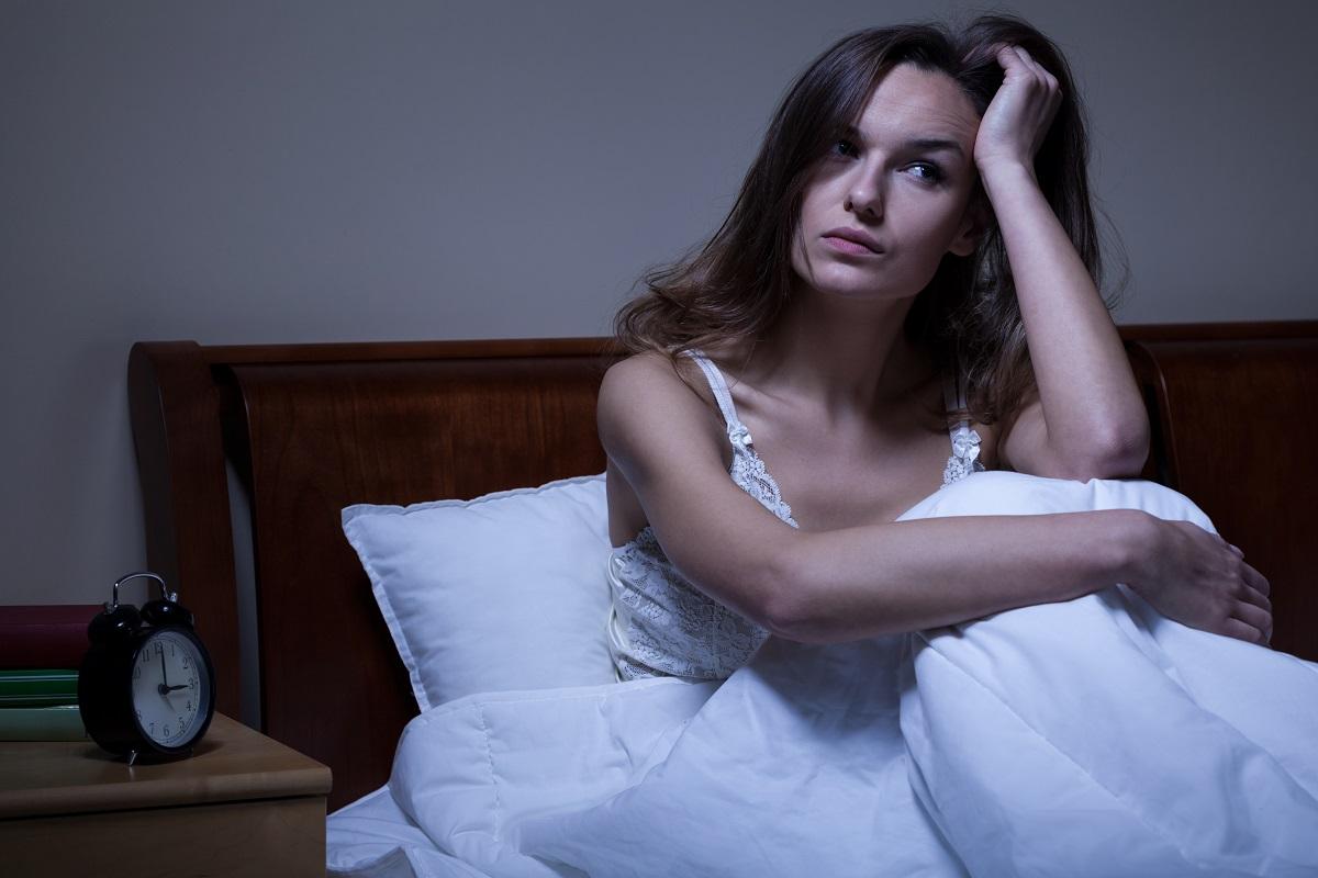 O femeie frumoasă care își ține o mână în păr în timp ce stă în pat supărată deaorece s-a trezit din timpul somnului noaptea