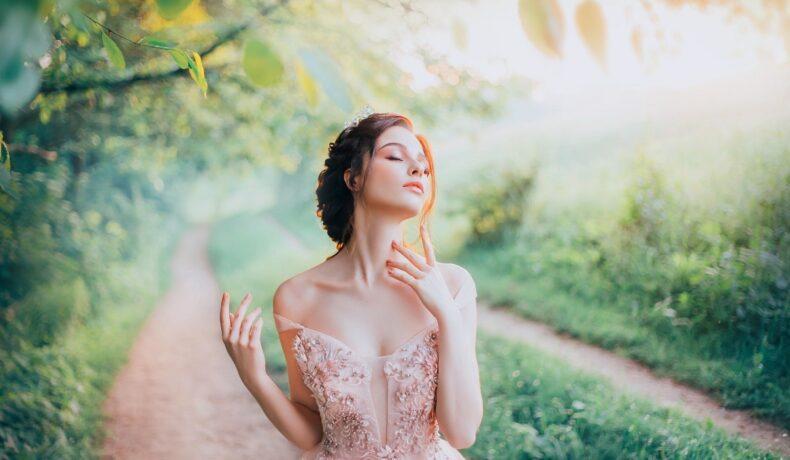 O femeie frumoasă într-un cadru feeric în timp ce poartă o rochie roz pudrat și se mângăie pe gât fiind una dintre cele mai dificile zodii