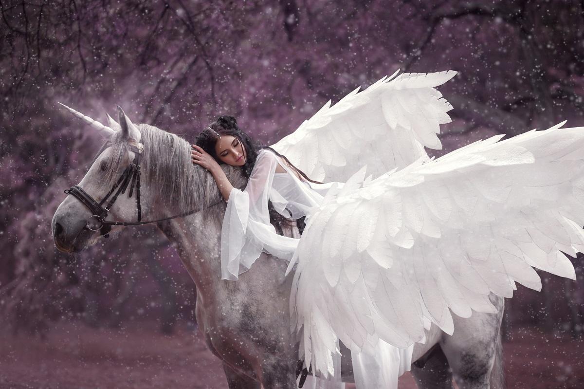 O femeie frumoasă care poartă o rochie albă și o pereche de aripi albe în timp ce stă întinsă pe un inorog într-o pădure feerică, simbolizând una din cele mai misterioase zodii