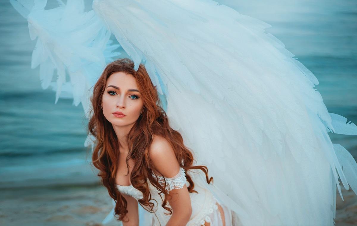 O femeie frumoasă cu părul lung și roșcat care poartă o rochie albă și are înspate aripi de înger în timp ce stă în genunchi pe o plajă reprezentând una dintre cele mai sincere zodii