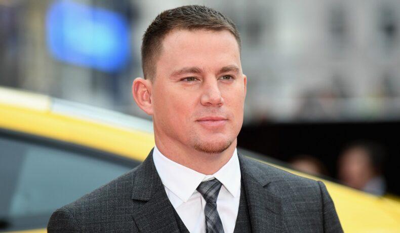 Portret al actorului Channing Tatum care poartă un costum gri și o cravată în timp ce participă la premiera peliculei Logan Lucky din anul 2017