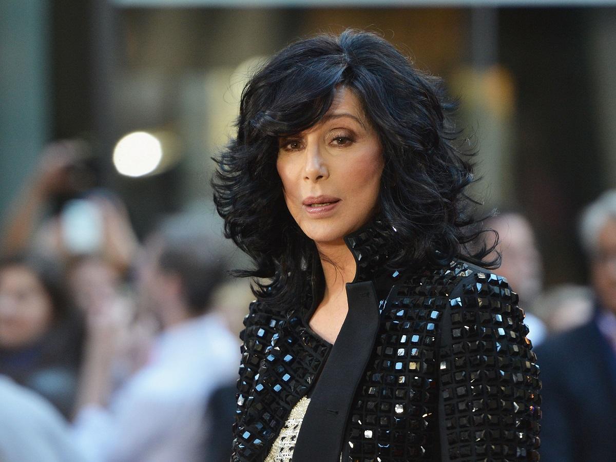 Cântăreața Cher cu părul scurt și ondulat în timp ce poartă o jachetă neagră cu pietre în anul 2013