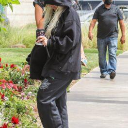 Christina Aguilera în timp ce se ascunde de fotografi și poartă un hanorac negru cu glugă pe cap și o pereche de pantaloni de trening