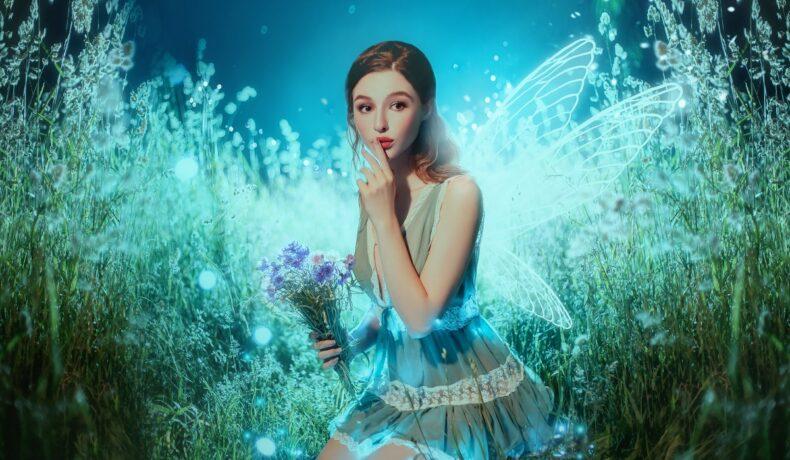 O zână cu rochie albastră care stă în iarbă în timp ce este luminată din spate