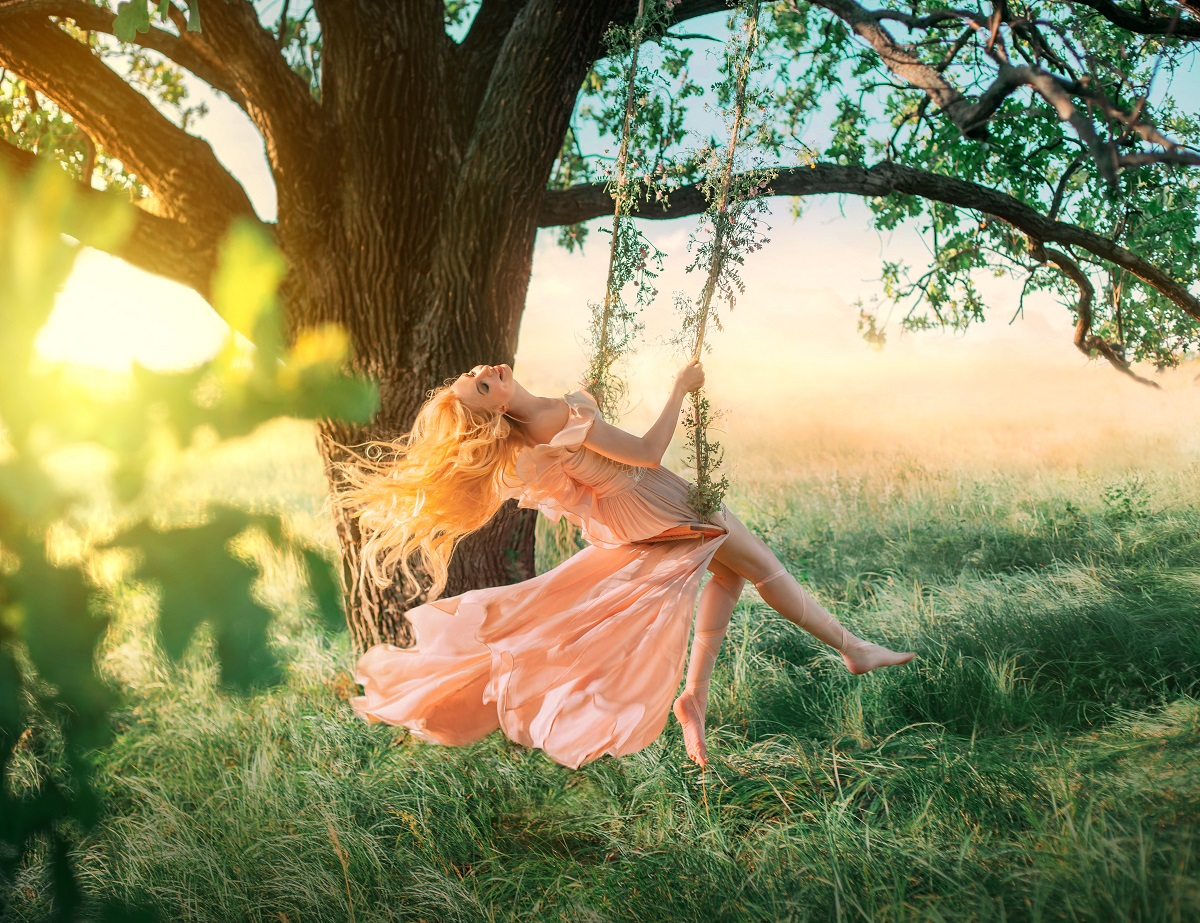 O femeie frumoasă care poartă o rochie în nuanță piersicie în timp ce se dă ântr-un leagă făcut într-un copac și care demonstrează cum percepe fiecare zodie în parte viața