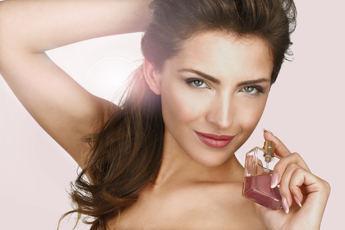 O femeie frumoasă cu părul prins care se dă cu un parfum roz