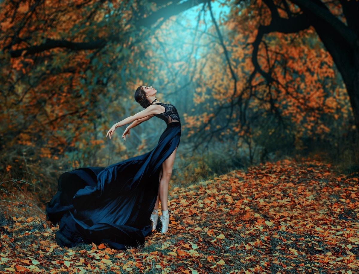 O femeie frumoasă balerină într-o rochie neagră în timp ce dansează balent într-o pădure