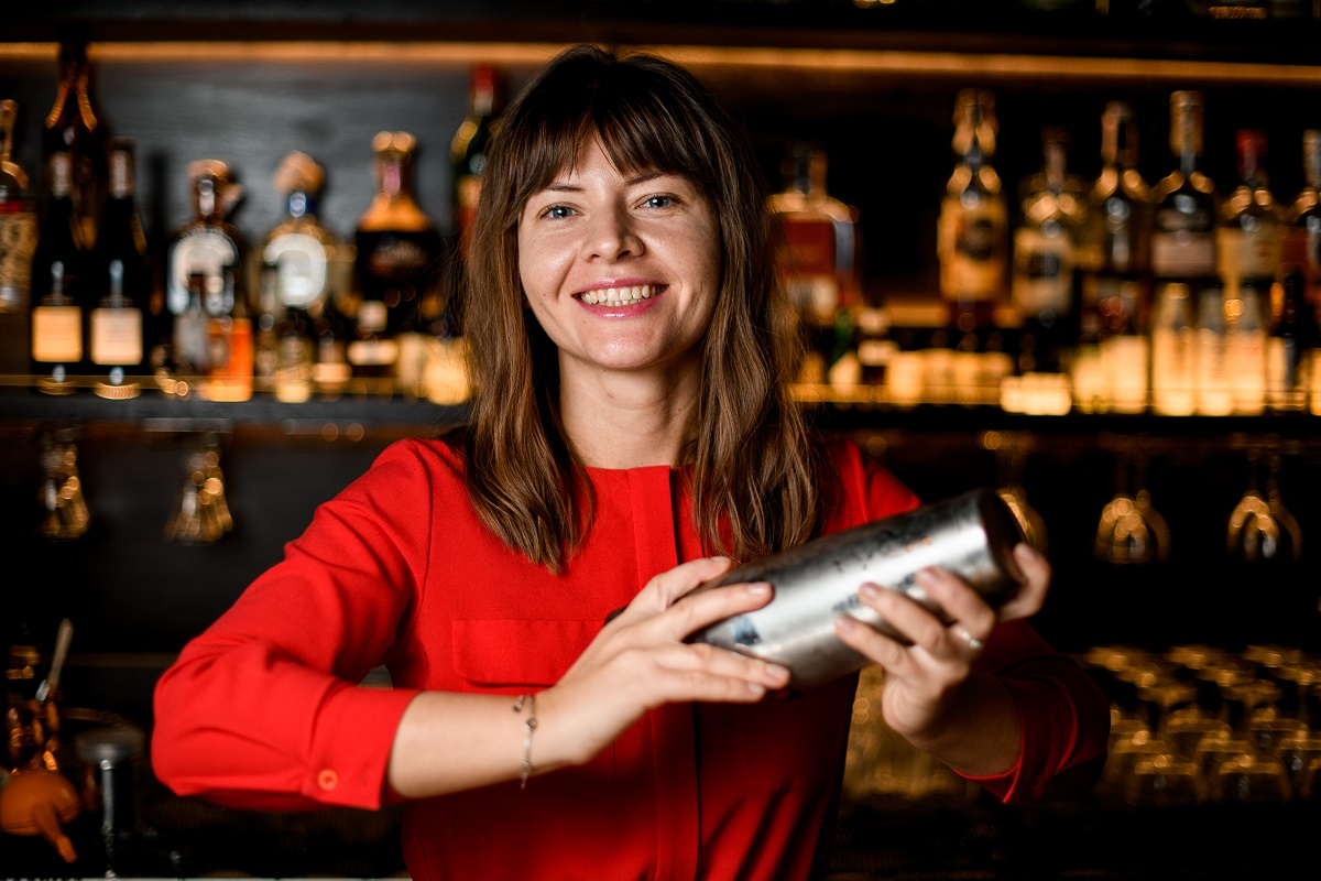 O femeie frumoasă care poartă o bluză roșie și prepară un cocktail cosmopolitan și zâmbește în timp ce se află în spatele unui bar
