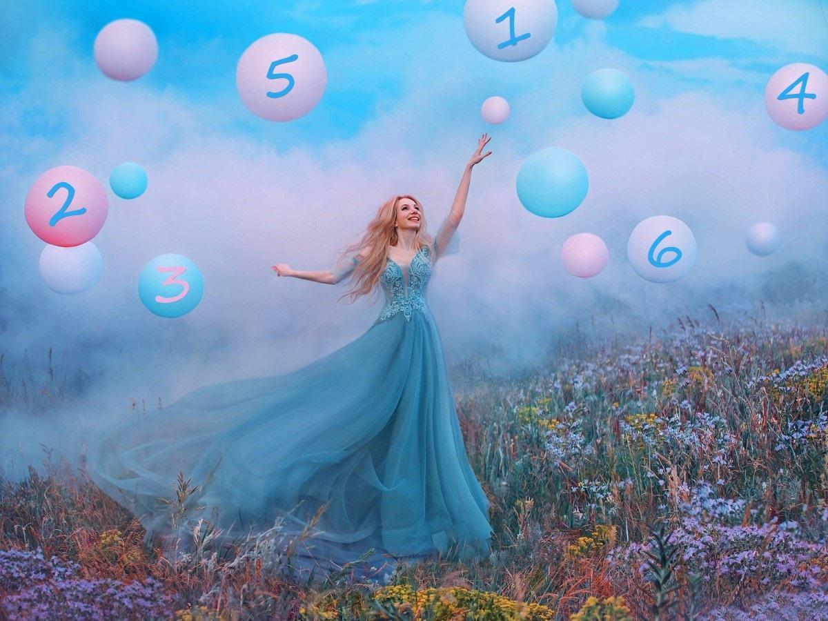 O femeie frumoasă într-o rochie albastră care se află pe o pajiște în timp ce întinde mâna către baloane colorate în roz și albastru pe care se află scrisă cifra destinului