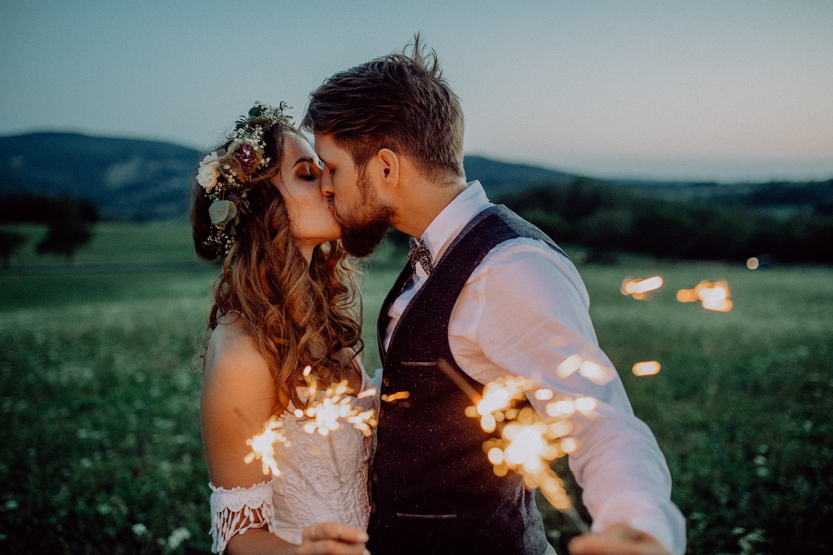 Un cuplu de îndrăgostiți în timp ce se sărută și țin în mână artificii pe un câmp liber