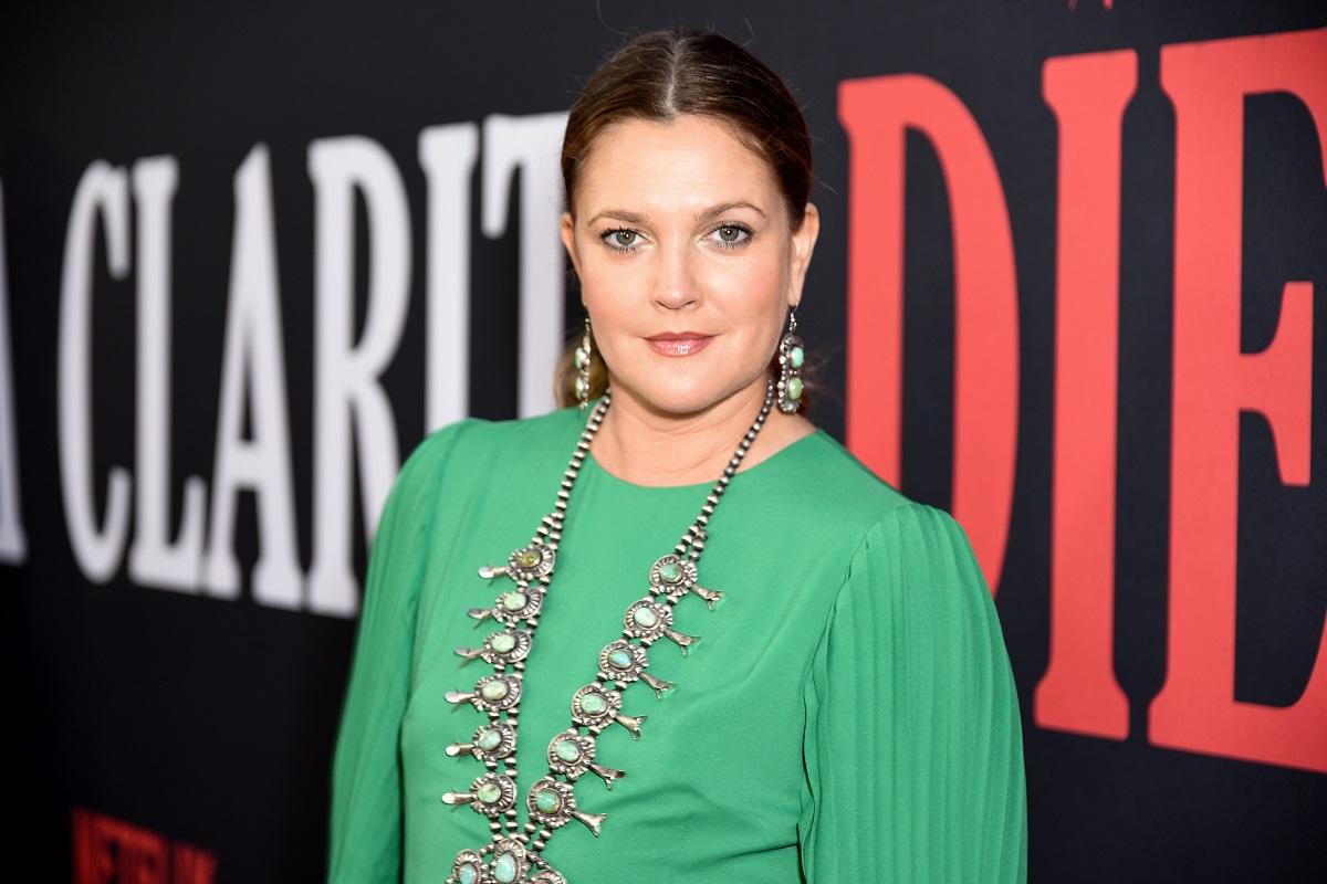 Drew Barrymore într-o rochie verde, cu părul prins în coadă și purtând un colier lung argintiu, în timp ce pozează pe covorul roșu la premiera show-ului Santa Clarita Diet