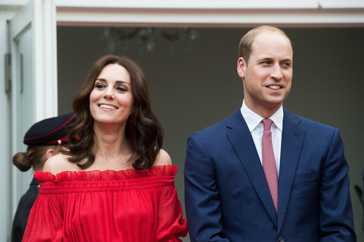 Kate Midlleton purtând o bluză roșie pe umeri alături de Prințul William care poartă un costum albastru în timp ce paticipă la un eveniment public