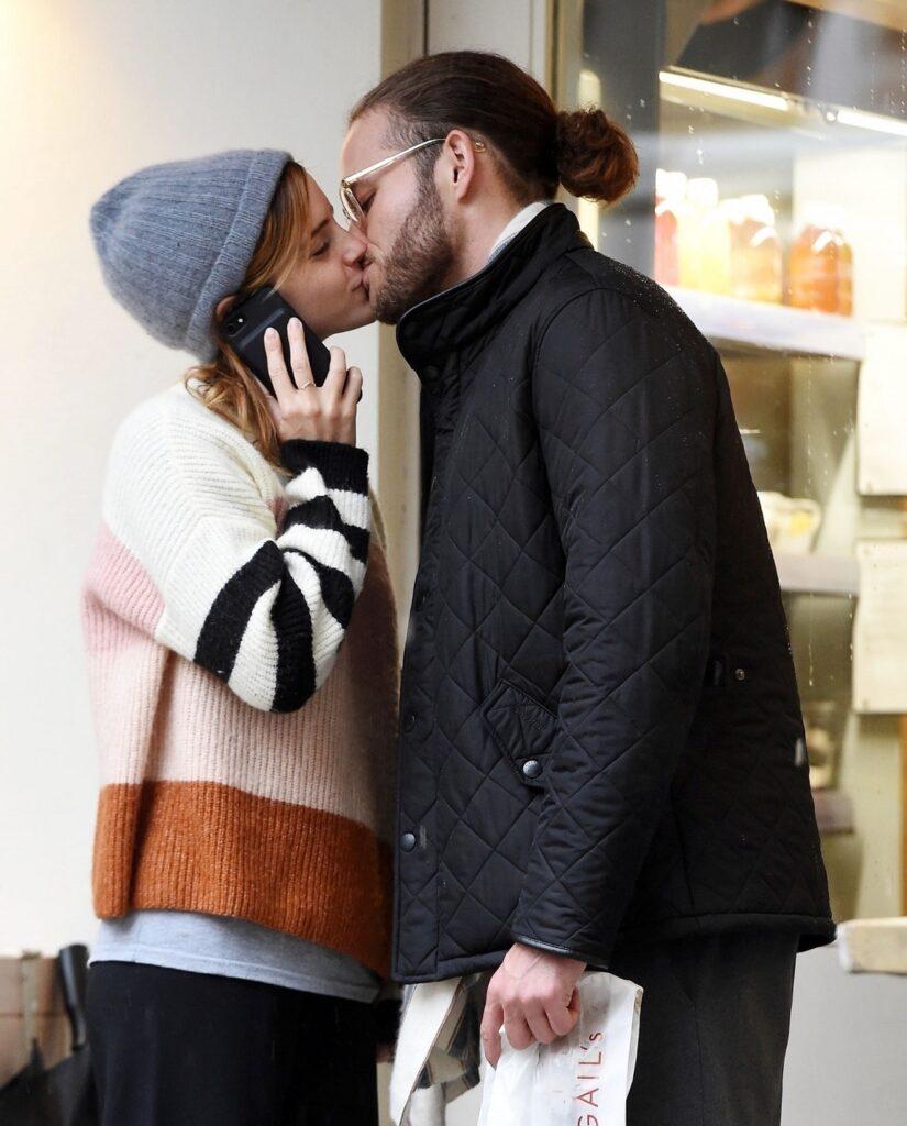 Emma Watson în timp ce poartă un pulover în dungi și o căciulă pe cap, sărutându-l pe iubitul său, Leo Robinton