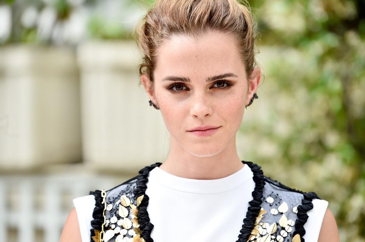 Emma Watson cu părul prins și purtând o rochie albă la Paris în anul 2017