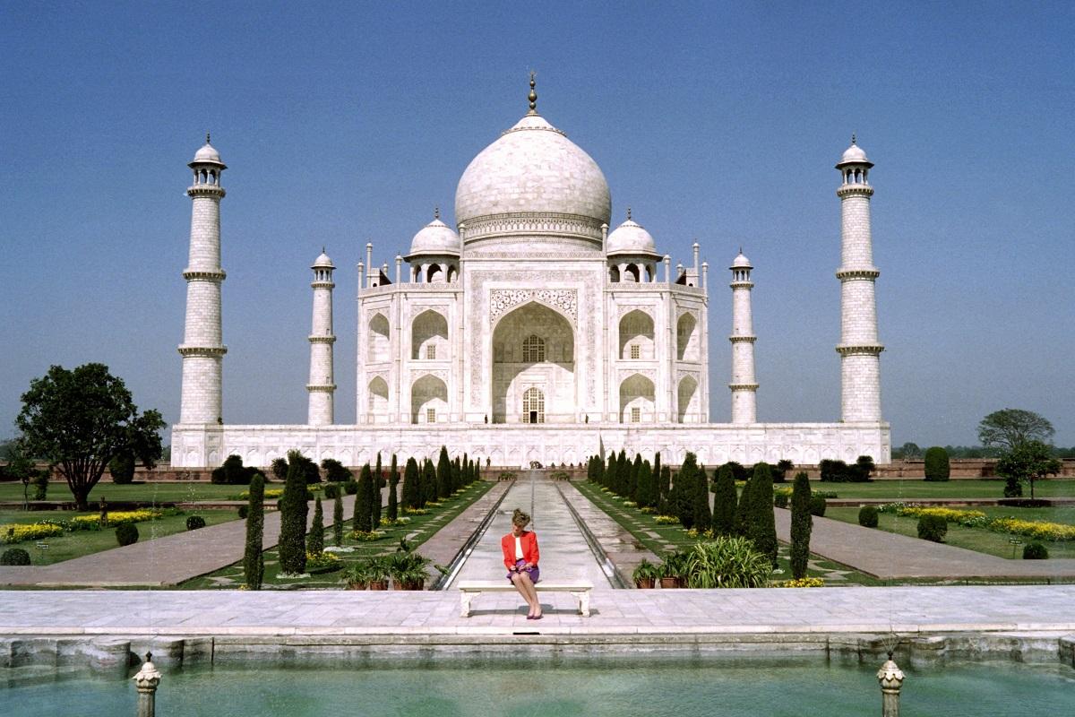 Prințesa Diana într-un sacou roșu și o fustă mov în timp ce stă pe o bancă în fața monumentului de la Taj Mahal