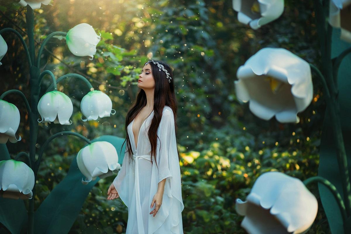 O femeie frumoasă îmbrăcată întro rochie albă în timp ce se află într-o pădure printre flori albe și se gândește care sunt acele gesturi pe care zodiile de aer le adoră într-o relație