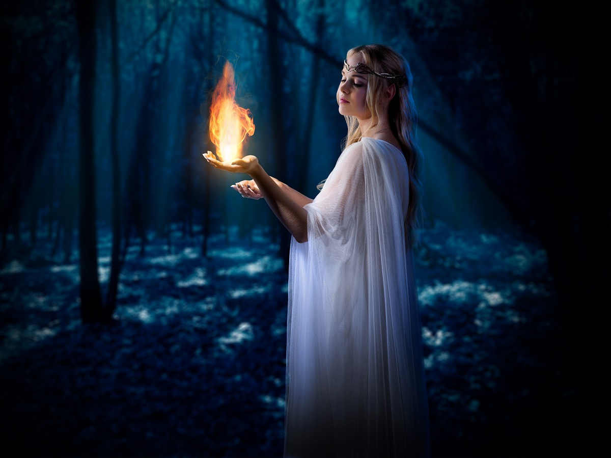 O femeie frumoasă într-o rochie albă care stă într-o pădure întunecată în tim ce ține în mână o flacără