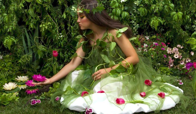 O femeie frumoasă care poartă o rochie albă împodobită cu frunze și flori și care culege flori de nufăr roz pentru a reprezenta acele gesturi pe care zodiile de pământ le adoră într-o relație