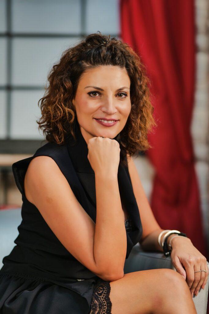 Portret al actriței Ioana Ginghină în timp ce stă pe un fotoliu picior peste picior și își ține sub bărbie pumnul