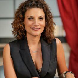 Ioana Ginghină în timp ce zâmbește la cameră pentru interviul de la CaTine.ro și poartă o vestă neagră