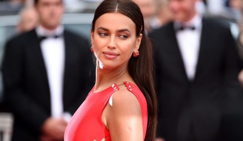 Portret al fotomodelului Irina Shayk în timp ce privește peste umăr într-o rochie roșie la festivalul de film de la Cannes din 2018