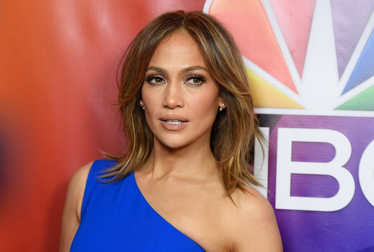Portret al vedetei Jennifer Lopez în timp ce poartă o rochie pe umăr albastră și privește la cameră la NBCUniversal Press Tour din 2016