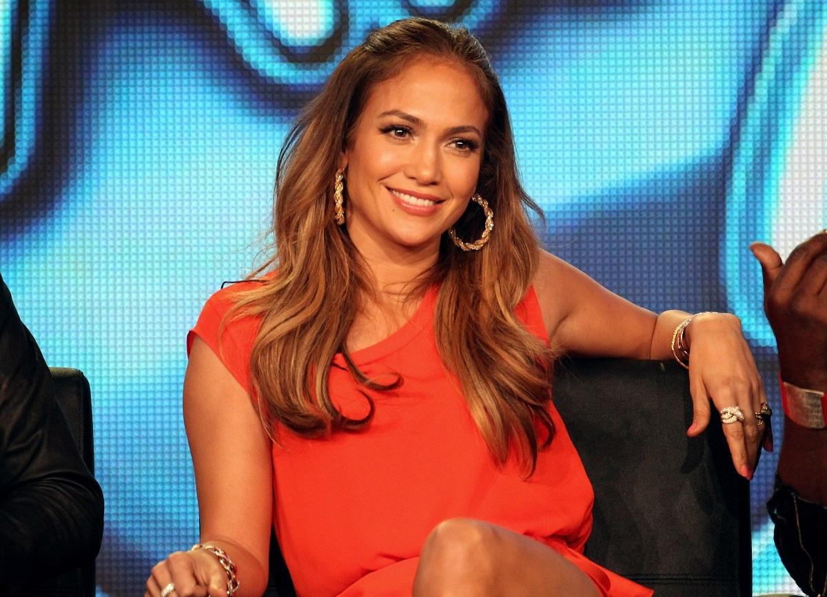 Artista Jennifer Lopez în timp ce stă pe un scaun într-o rochie portocalie și zâmbește la cameră în anul 2012