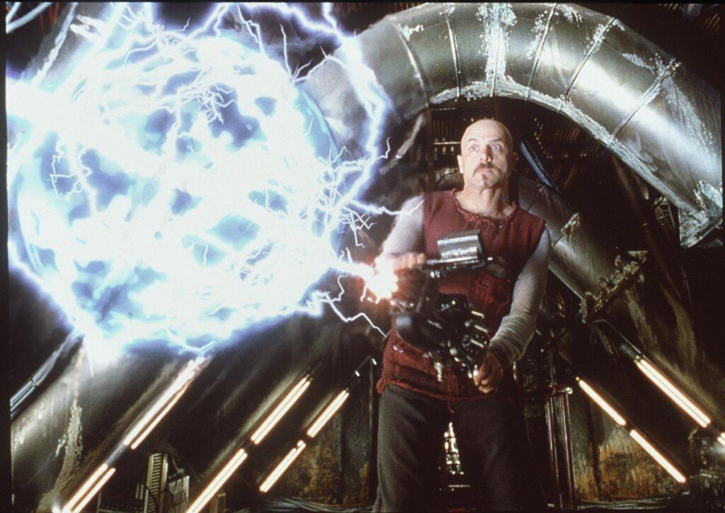Actorul Joe Pantolino ținând în mână un furtun electric într-o scenă din filmul Matrix din 1999