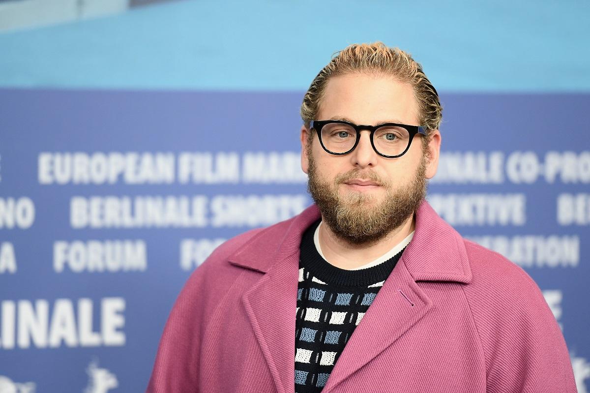 Jonah Hill într-o bluză în carouri cu un palton roz peste în timp ce participă la premiera unui film în Germania în anul 2019