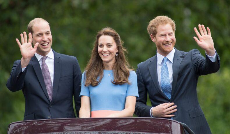 Prințul William la costum în timpce face cu mâna, alături de Ducesa Kate Middleton și Prințul Harry în timpul aniversării a 90 de ani împliniți de Regina Elisabeta