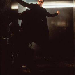 Actorul Keanu Reeves într-un costum negru în timp ce sare în aer și lovește cu piciorul un bărbat într-o scenă din filmul Matrix