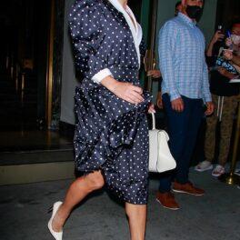 Lady Gaga în timp ce iese din hotel din New York și poartă o rochie albastră cu buline albe, o pereche de tocuri albe și o poșetă mică albă