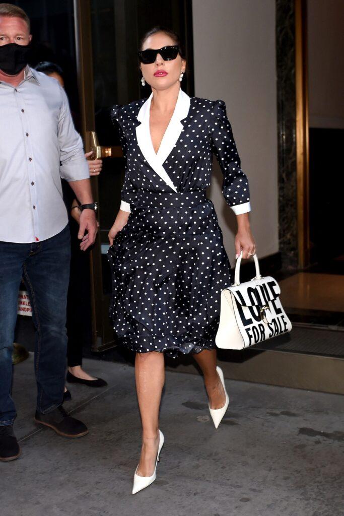 Lady Gaga în timp ce poartă o rochie neagră cu buline albe după ce s-a inspirat din look-ul Ducesei de Cambridge și iese dintr-o clădire pe străzile din New York