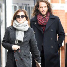 Emma Watson purtând un palton gri, un fular și o pereche de ochelari de soare în timp ce merge pe stradă alături de iubitul său, Leo Robinton care poartă un palton negru