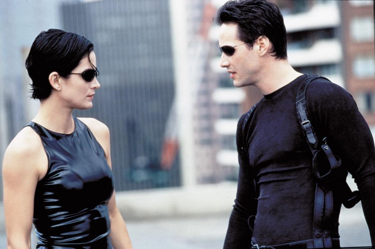 Keanu Reeves și Carrie-Anne Moss îmbrăcați în ținute negre într-o scenă din filmul Matrix din 1999