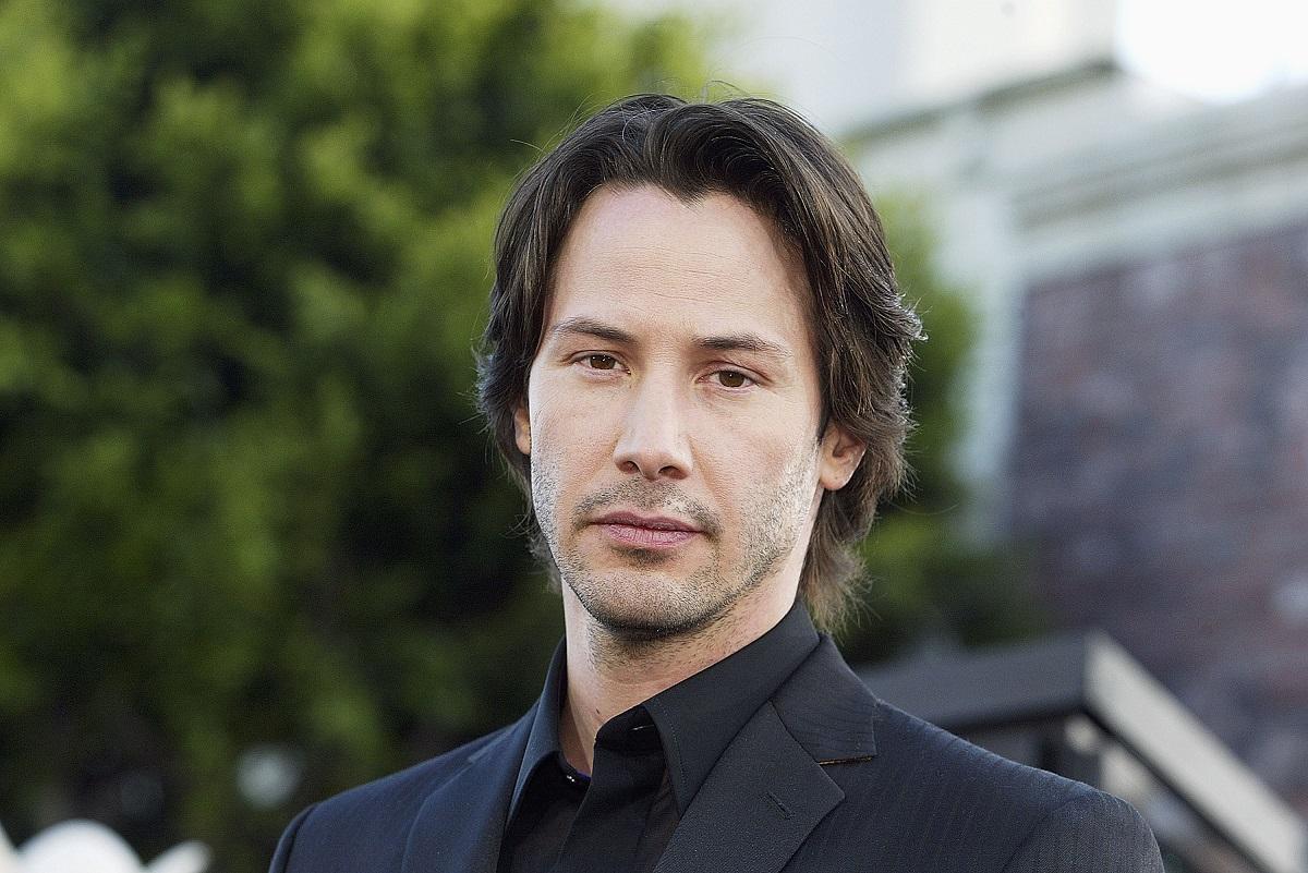 Keanu Reeves îmbrăcat la costum în timp ce ia parte la premiera The Matrix din anul 2003